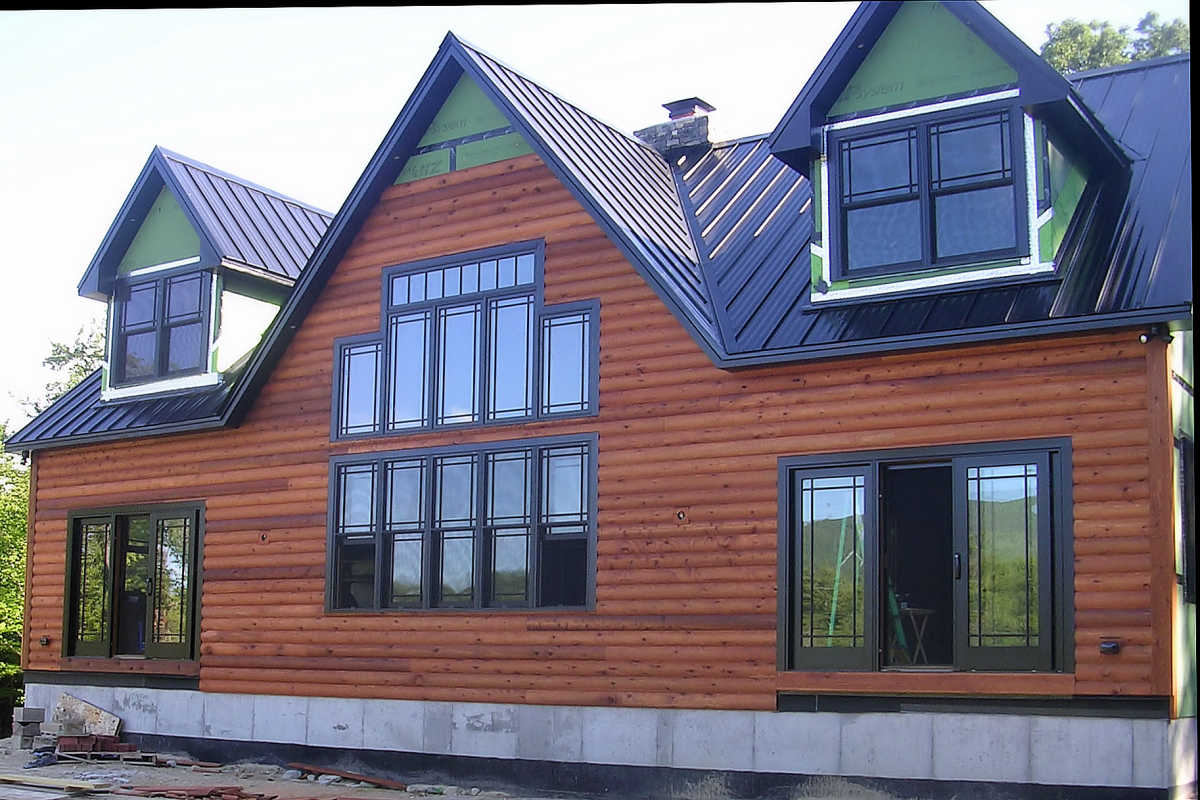 New Hampshire home during installation of 2x8 Cedar Cabin Log Siding Finished TWP Rustic Semi -trans stain